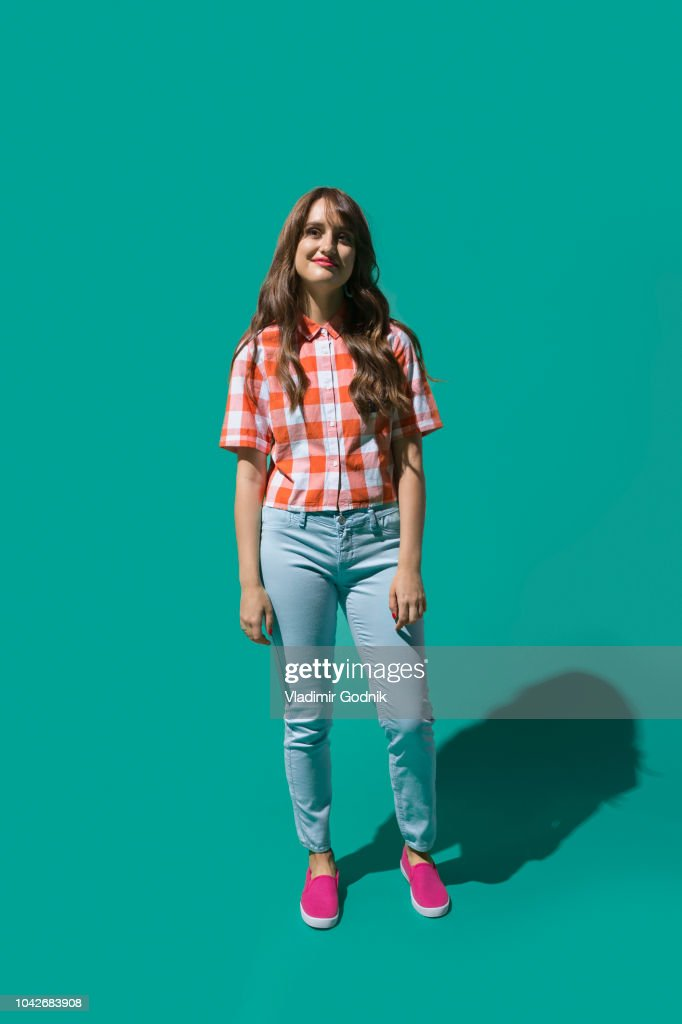 Portrait confident young woman against turquoise background : Stock Photo