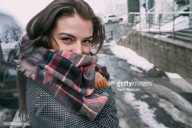 portrait confident young woman in plaid scarf on snowy winter street - sjaal stockfoto's en -beelden