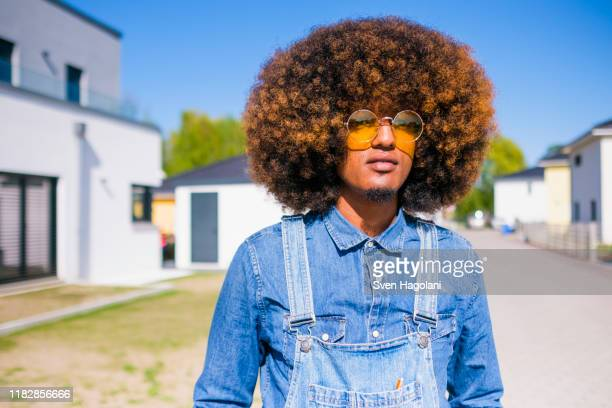 portrait cool young man with afro in denim overalls standing on sunny road - jeansstoff stock-fotos und bilder