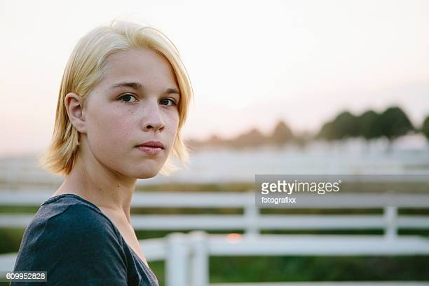 portrait: cute blonde teenager girl looks seriously at the camera