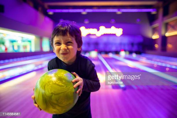 portrait cute child with ball in bowling club - bowling stock pictures, royalty-free photos & images