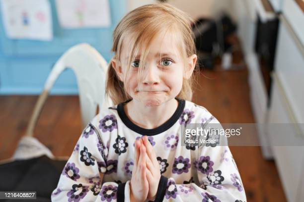portrait cute girl pleading with hands clasped - suplicar imagens e fotografias de stock