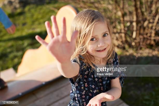 portrait cute girl waving at sunny playground - 6 7 jahre stock-fotos und bilder