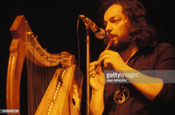 Portrait d'Alan Stivell jouant de la flûte droite tin whistle avec à gauche sa harpe celtique lors d'un concert circa 1970 en France
