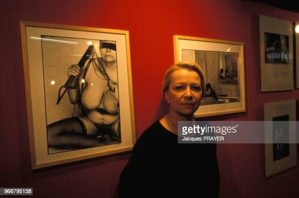 Portrait de Claude Alexandre photographe sadomasochiste devant ses oeuvres au Salon de l'Erotisme le 24 mars 1985 à Paris France