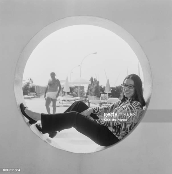 Portrait de la chanteuse Nana Mouskouri assise sur le rebord d'une fenêtre en hublot près d'une plage de Cannes le 25 juillet 1969 en France