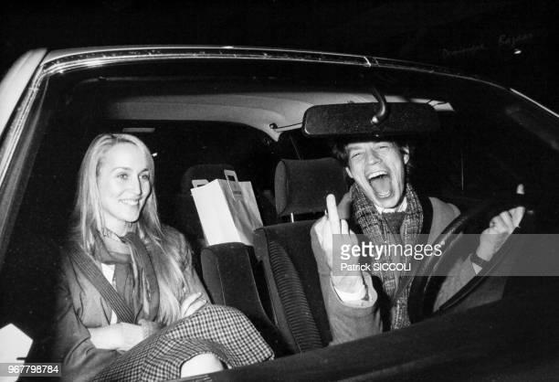 Portrait de la mannequin Jerry Hall et du chanteur anglais Mick Jagger faisant un doigt d'honneur au volant d'une voiture le 21 novembre 1982 à Paris...