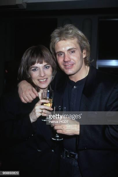 Portrait de l'actrice Nicole Calfan et de son époux le chanteur François Valéry buvant du champagne à l'Olympia en 1990 à Paris, France.