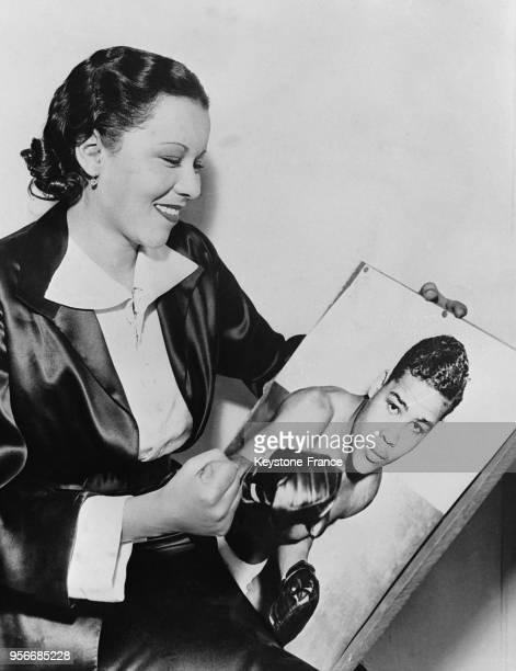 Portrait de Marva Trotter épouse du boxer Joe Louis tenant une photographie de son mari aux EtatsUnis en 1935