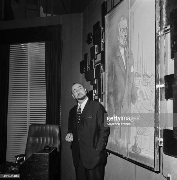 Portrait de Pierre Brasseur devant un tableau le représentant circa 1969