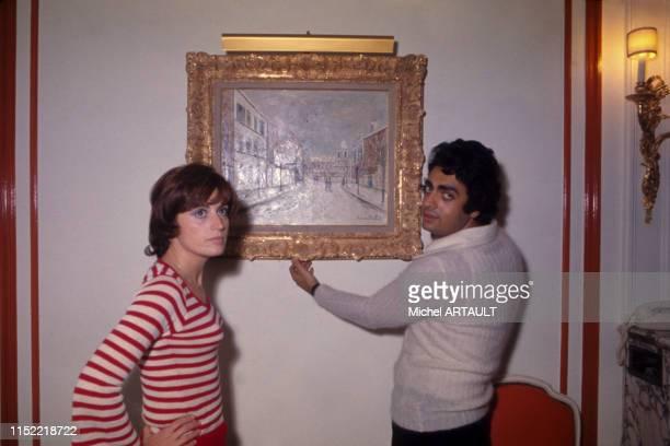Portrait d'Enrico Macias avec sa femme Suzy accrochent un tableau chez eux à Paris dans les années 70 France Circa 1970
