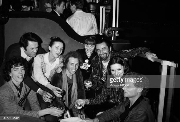 Portrait des comédiens et danseurs Robert Hirsch, Maurice Béjart, Jorge Donn et Ludmila Mikaël en compagnie d'autres danseurs et artistes dînant au...