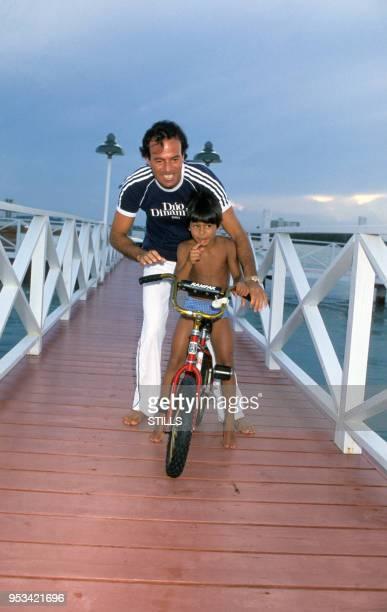 Portrait du chanteur espagnol Julio Iglesias et de son fils sur un vélo sur une jetée près de la mer, circa 1980.