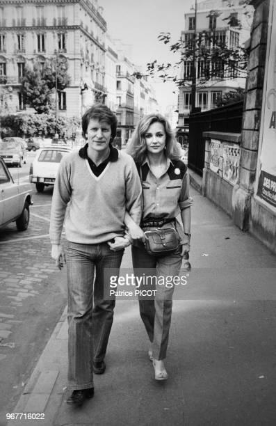 Portrait du comédien André Dussollier et de la comédienne Caroline Cellier se promenant dans les rues le 23 mai 1980 en France