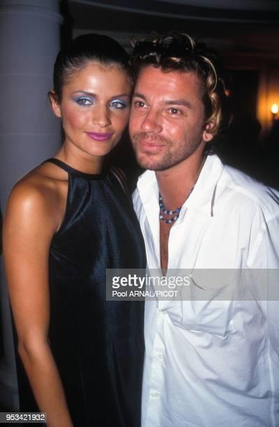 Portrait du mannequin Helena Christensen en compagnie du chanteur australien Michael Hutchence au défilé de haute-couture du couturier Yves...
