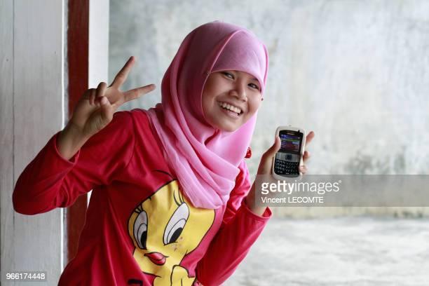 Portrait dune adolescente indonésienne voilée avec son smartphone faisant un signe de victoire avec une main à l'école de Basca à Painan au sud de...