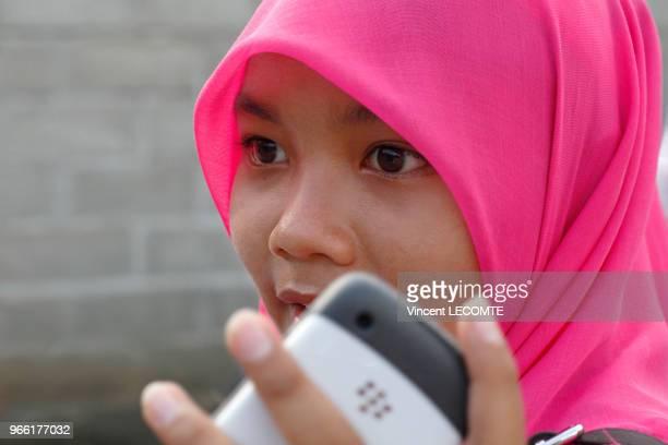 Portrait dune adolescente indonésienne voilée avec son smatphone à la main à Painan au sud de lîle de Sumatra en Indonésie le 24 septembre 2012