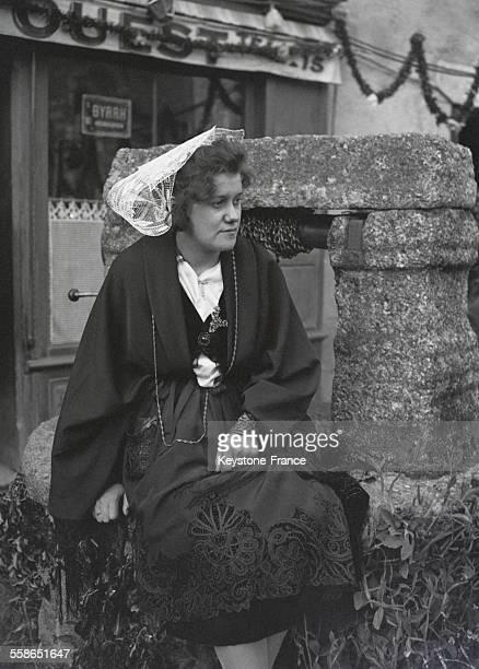 Portrait d'une bretonne en costume et coiffe traditionnels assise sur la margelle d'un puits en Bretagne France circa 1930