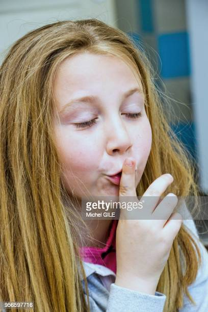 Portrait d'une fillette de sept ans faisant 'chut' pour demander le silence avec le doigt devant la bouche