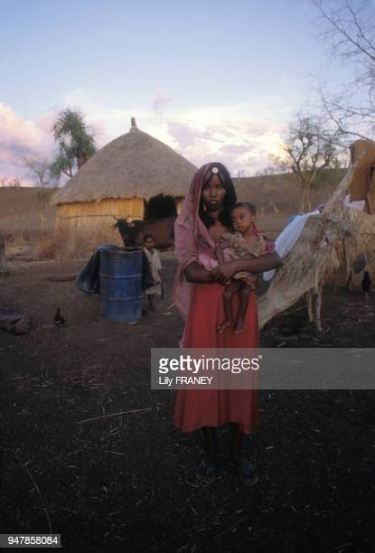 Portrait d'une jeune femme en costume traditionnel portant un enfant dans ses bras en 1988 au Soudan