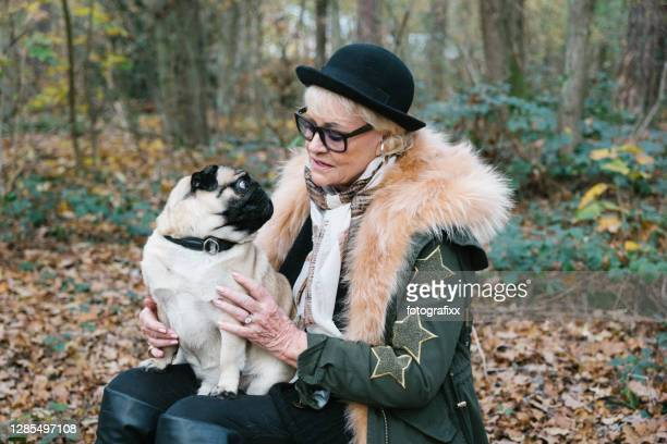 portrait: elegant elderly woman with her pug in the forest - glamour stock pictures, royalty-free photos & images
