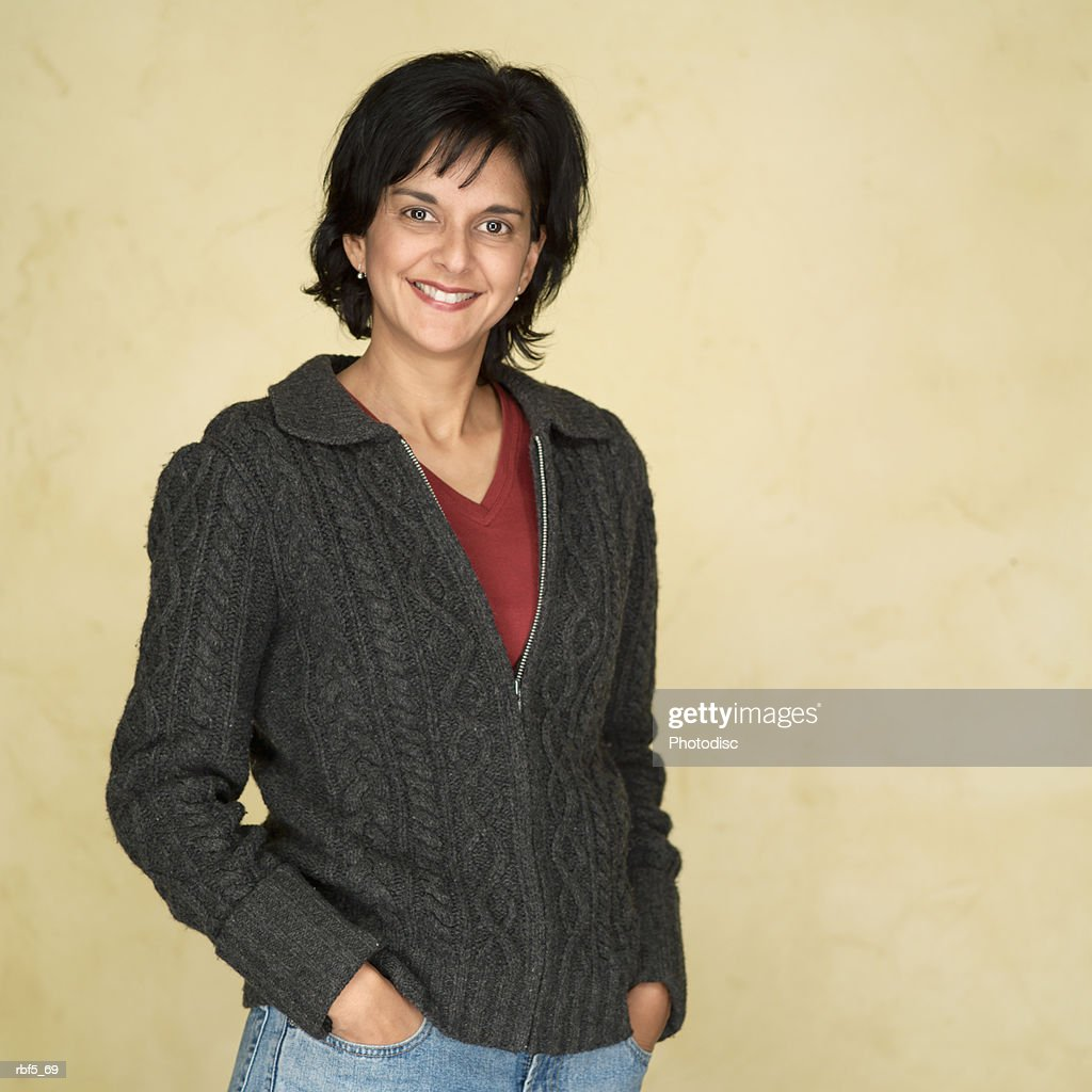 portrait ethnic looking woman in red shirt grey sweater she puts her hands in pockets and smiles : Stockfoto