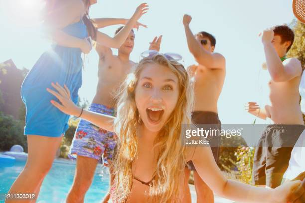 portrait exuberant teenage girl dancing with friends at sunny summer poolside - incidental people stock pictures, royalty-free photos & images