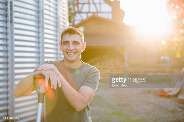 Portrait: Farmer on his farm next to a silo