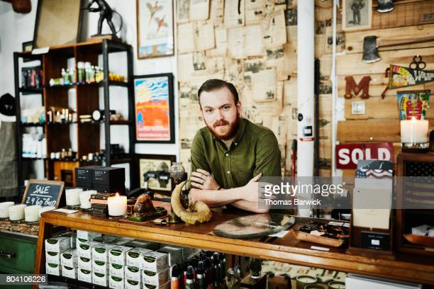 Portrait for shop owner behind counter in mens boutique