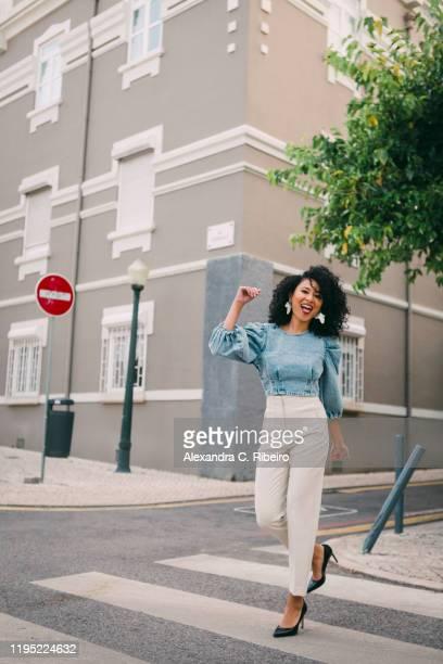 portrait happy, carefree woman crossing city street - 斜めから見た図 ストックフォトと画像