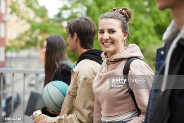 portrait happy female teenager with friends in city - 18 19 years stock pictures, royalty-free photos & images