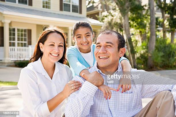 Portrait happy Hispanic family sitting with house in background