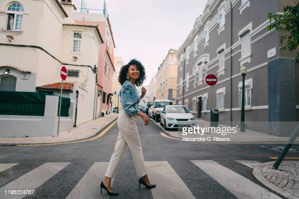 portrait happy, stylish woman crossing city street - posing shoes stock pictures, royalty-free photos & images