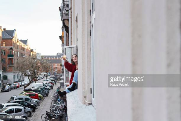 portrait happy young woman with cocktail in apartment window during covid-19 isolation - focus on background stock pictures, royalty-free photos & images