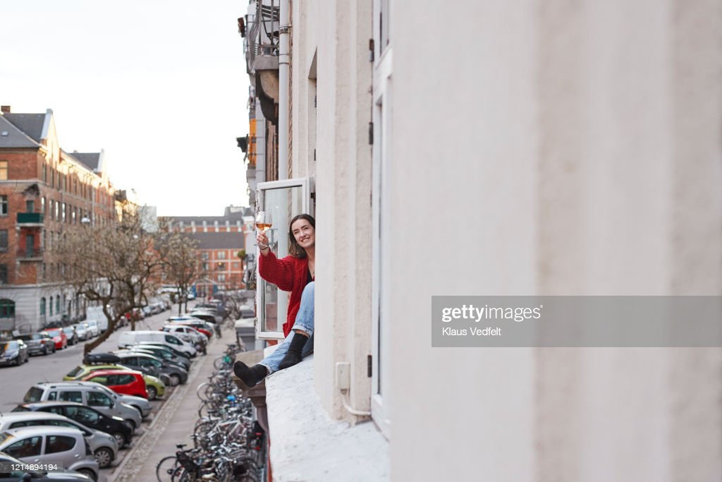 Portrait happy young woman with wine in apartment window : Stockfoto