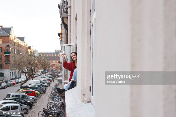 portrait happy young woman with wine in apartment window - ロックダウン ストックフォトと画像