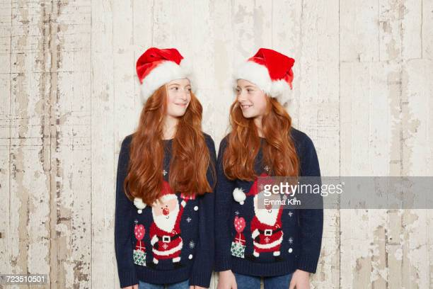 Portrait if twin sisters wearing Christmas jumpers and hats