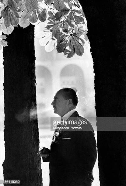 Portrait in profile of the Italian hermetic poet Salvatore Quasimodo elegantly dressed with a jacket and tie whil ehe is smoking a cigarette Milan...