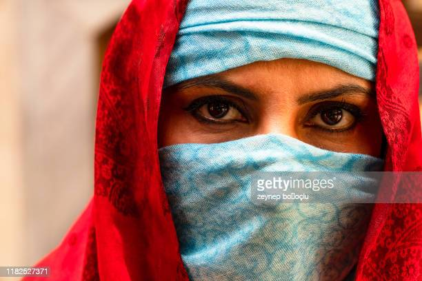 portrait in the shawl. east woman a portrait, young middle eastern woman in hijab with sexy black eyes. beautiful brunette woman in red and blue headscarf - nikab stock pictures, royalty-free photos & images