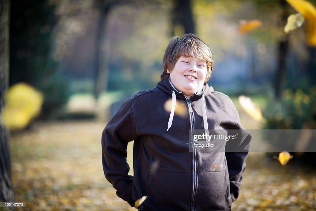 Retrato de um menino sorrindo em fundo de natureza com excesso de peso : Foto de stock