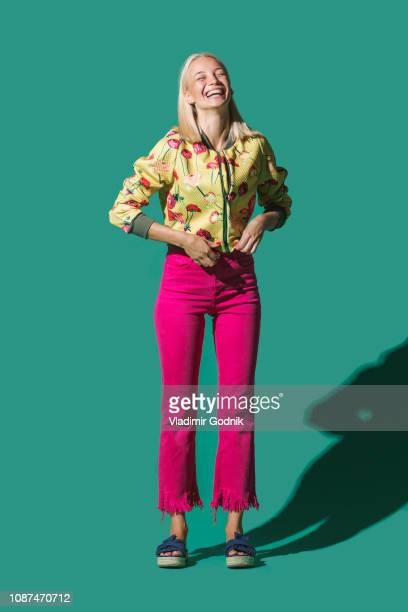 portrait laughing woman against green background - studiofoto stockfoto's en -beelden