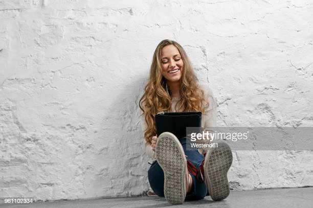 portrait laughing young woman sitting on the floor using tablet - soles pose stockfoto's en -beelden