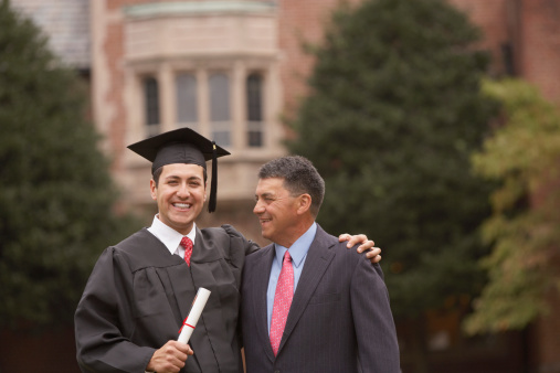 Portrait male graduate in cap and gown with diploma with father - gettyimageskorea