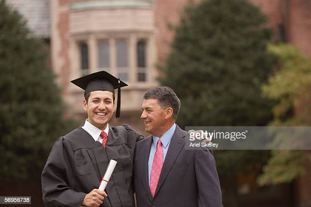 Portrait male graduate in cap and gown with diploma with father