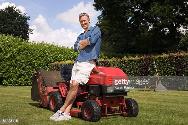 Portrait man standing by lawn mower