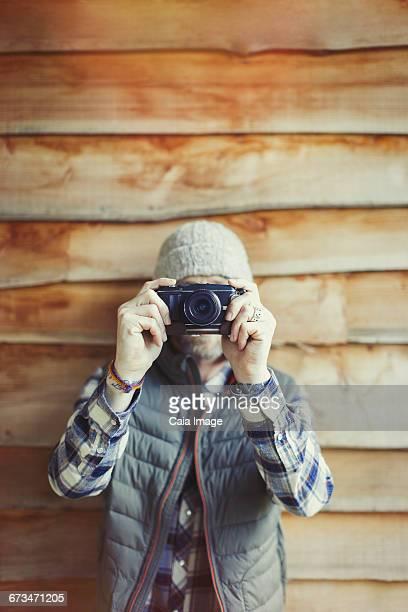 Portrait man using camera outside cabin
