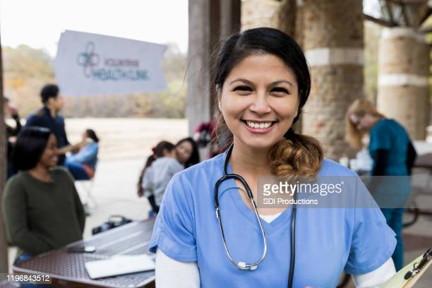 portrait mid adult female volunteer doctor at free clinic - community health stock pictures, royalty-free photos & images
