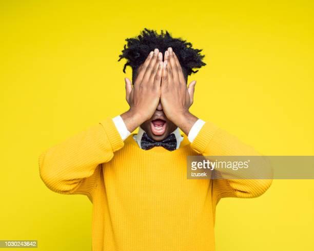porträt nerdy junge manndeckung augen mit händen - augen zuhalten stock-fotos und bilder