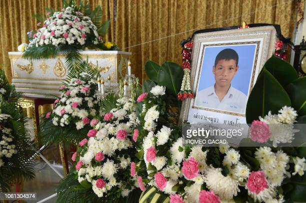 A portrait of 13yearold Muay Thai boxer Anucha Tasako is displayed next to his coffin during a funeral at a Buddhist temple in Samut Prakan province...