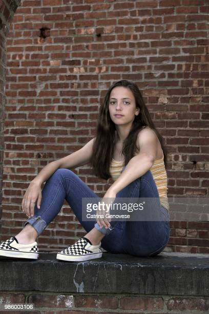Portrait of 16 year old teenage girl seated in brick arch window opening against brick wall background
